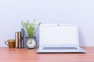 laptop, wekker en bloem op het bureau