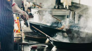 chef-kok die roerbak in een wok maakt