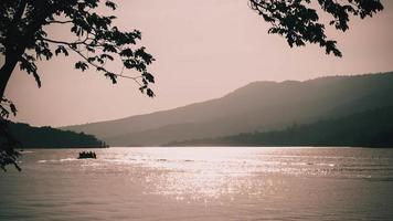 lichtreflectie door oppervlaktegolven van een meer bij zonsondergang met bergachtergrond. foto