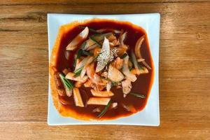 heerlijke Koreaanse pittige tteokbokki. het beeld van pittige tteokbokki op hout achtergrond foto
