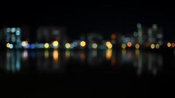 kleurrijke bokeh van de skyline van de stad vanaf de rivier in de nacht