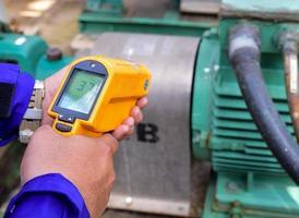 het meten van de temperatuur van de motor met infraroodthermometer foto