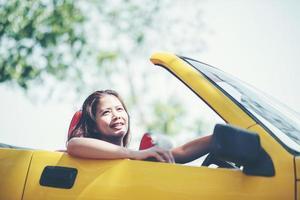 gelukkige vrouw genieten van de top-down in cabriolet foto