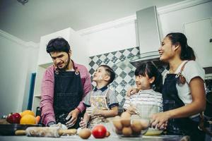 gelukkige familie genieten van hun tijd samen koken in de keuken foto