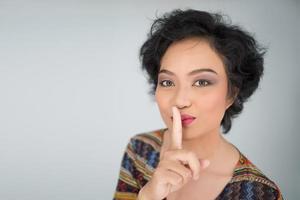 jonge vrouw maakt stil gebaar op witte achtergrond