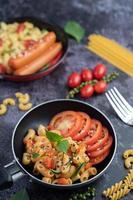 gebakken macaroni en worst in een koekenpan foto