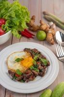 roergebakken varkensvlees met basilicum en gebakken ei