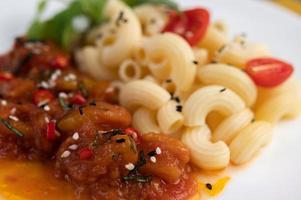 roergebakken macaroni met tomaat, chili, peperzaadjes en basilicum