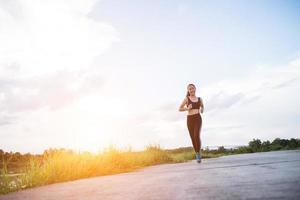 een jonge gelukkige vrouwelijke atleet die buitenshuis jogt