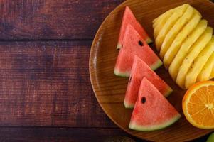watermeloen, sinaasappel en ananas in stukjes gesneden op een houten plaat
