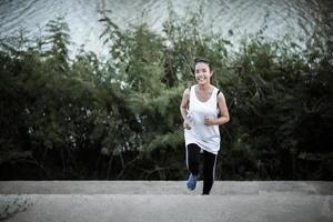 een jonge gelukkige vrouwelijke atleet die buitenshuis jogt foto