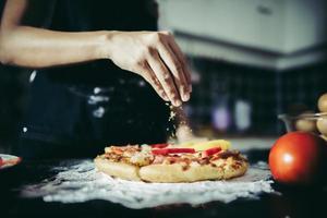 close-up van een hand oregano zetten over een pizza