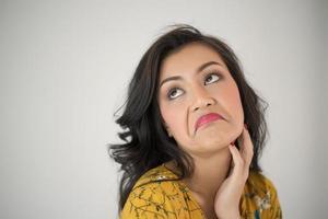 jonge vrouw die expressief gezicht geeft op witte achtergrond foto