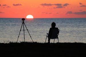 een fotograafvrouw die naar de zon kijkt foto