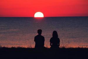 twee personen kijken naar de zonsondergang foto