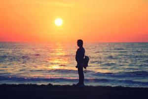een meisje dat naar de zonsondergang kijkt foto