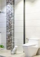 moderne ruime badkamer met lichte tegels voorzien van glazen douchecabine, toilet en wastafel. zijaanzicht foto