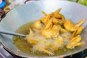 huisgemaakt koken van gefrituurde kippenvleugels in pan. foto