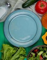 bovenaanzicht van gesneden en hele groenten als sla, komkommer, basilicum, tomaat met zout, zwarte peper en lege plaat op groene achtergrond foto