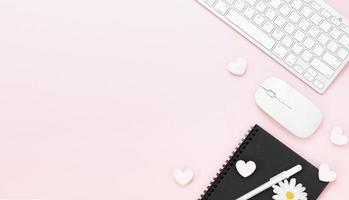 minimale bureautafel met hart paperclip, toetsenbordcomputer, muis, witte pen, katoenen bloemen, gum op een roze pasteltafel met kopie ruimte voor het invoeren van uw tekst, valentijnsdag concept, plat leggen, bovenaanzicht foto