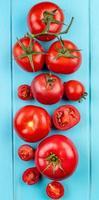 bovenaanzicht van gesneden en hele tomaten op blauwe achtergrond