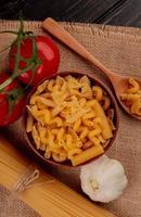 Bovenaanzicht van verschillende soorten macaroni in kom met vermicelli type tomaten houten lepel en knoflook op zak en houten achtergrond foto