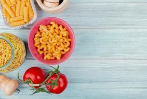 bovenaanzicht van verschillende soorten macaroni als cavatappi ziti spaghetti met tomatenzout op houten achtergrond met kopie ruimte