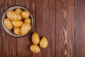 bovenaanzicht van nieuwe aardappelen in kom op houten achtergrond met kopie ruimte