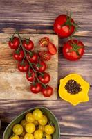 bovenaanzicht van gesneden en hele tomaten op snijplank met andere zwarte peper zaden op houten achtergrond