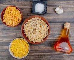 bovenaanzicht van verschillende macaronis als spaghetti tagliatelle en anderen met zoute knoflook gesmolten boter op houten achtergrond foto