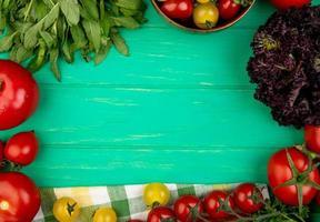 groenten met groene muntblaadjes tomaat basilicum op groene achtergrond foto