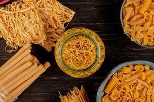 bovenaanzicht van verschillende soorten macaroni als bucatini spaghetti vermicelli tagliatelle en anderen op houten achtergrond