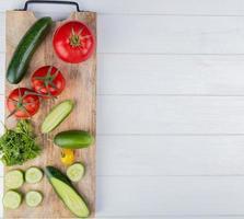 bovenaanzicht van groenten als komkommer tomaat koriander op snijplank aan de linkerkant en houten achtergrond met kopie ruimte foto