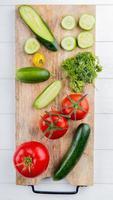 bovenaanzicht van groenten als komkommer tomaat koriander op snijplank op houten achtergrond foto