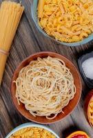 bovenaanzicht van verschillende macaronis als spaghetti rotini vermicelli en anderen met zout en ketchup op houten achtergrond foto