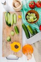 bovenaanzicht van hele gesneden en gesneden komkommers en zwarte peper op snijplank met tomaten kom met plakjes komkommer en komkommers op doek met zout knoflook crusher gesmolten olie op houten achtergrond