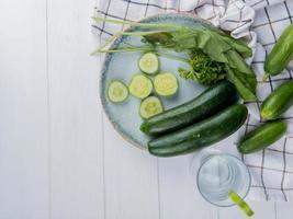 bovenaanzicht van groenten als geheel en gesneden komkommer spinazie koriander met komkommers op doek en detox water op houten achtergrond met kopie ruimte foto