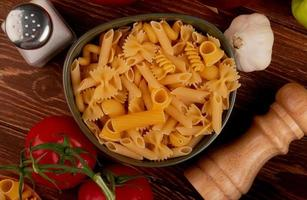 bovenaanzicht van verschillende macaronis in kom met zoute tomaat knoflook op houten achtergrond