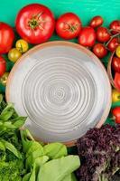 bovenaanzicht van groenten als tomaat, koriander, spinazie, basilicum met plaat op groene achtergrond foto