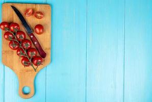 bovenaanzicht van gesneden en hele tomaten met mes op snijplank op blauwe achtergrond met kopie ruimte