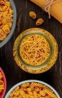 bovenaanzicht van verschillende macaronis als vermicelli rotini en anderen in pot en kommen op houten achtergrond