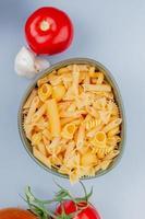 bovenaanzicht van verschillende soorten macaroni in kom met tomaat knoflook op blauwe achtergrond
