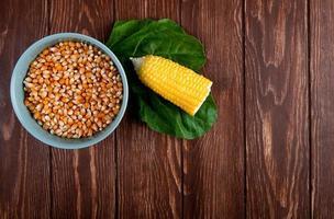 bovenaanzicht van kom vol gedroogde maïskorrel met gesneden gekookte maïs en spinazie op houten achtergrond met kopie ruimte