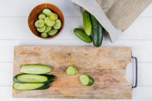 Bovenaanzicht van gesneden en gesneden komkommer op snijplank met kom met plakjes komkommer en komkommers morsen uit zak op houten achtergrond foto