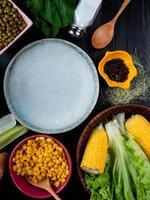 bovenaanzicht van gekookte likdoorns maïs zaden lege plaat sla met maïs zijde zout lepel spinazie op zwarte achtergrond