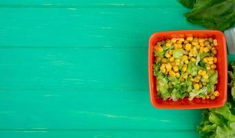 Bovenaanzicht van kom gele erwt met gesneden sla en spinazie hele sla aan de rechterkant en groene achtergrond met kopie ruimte