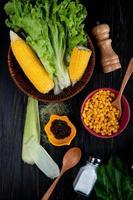 bovenaanzicht van gekookte likdoorns maïs zaden sla met maïsschaal en zijde zout lepel spinazie op zwarte achtergrond