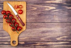 bovenaanzicht van gesneden en hele tomaten met mes op snijplank op houten achtergrond met kopie ruimte foto