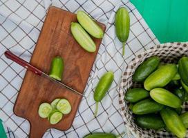 bovenaanzicht van gesneden en gesneden komkommer met mes op snijplank met hele in mand op geruite doek en groene achtergrond foto