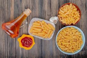 bovenaanzicht van verschillende macaronis als ziti rotini en anderen met knoflook gesmolten boter en ketchup op houten achtergrond foto